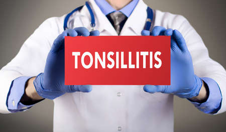 aching: Doctors hands in blue gloves shows the word tonsillitis. Medical concept.