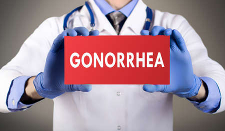 Doctors hands in blue gloves shows the word gonorrhea. Medical concept.