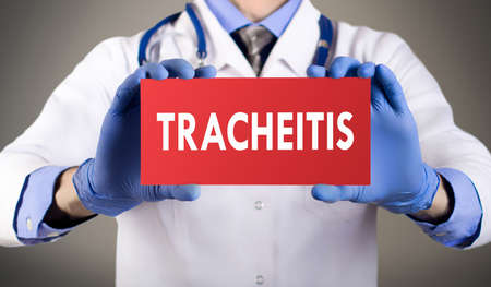 latent: Doctors hands in blue gloves shows the word tracheitis. Medical concept.
