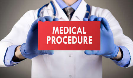 medical procedure: Doctors hands in blue gloves shows the word medical procedure. Medical concept. Stock Photo