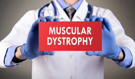 dystrophy: Doctors hands in blue gloves shows the word muscular dystrophy. Medical concept.