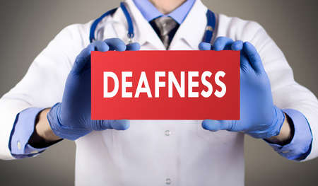 deafness: Doctors hands in blue gloves shows the word deafness. Medical concept. Stock Photo