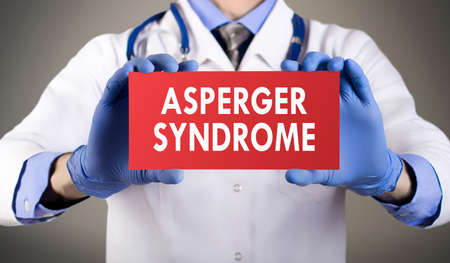 asperger syndrome: Doctors hands in blue gloves shows the word asperger syndrome. Medical concept. Stock Photo