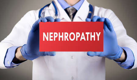 Doctors hands in blue gloves shows the word nephropathy. Medical concept. Stock Photo