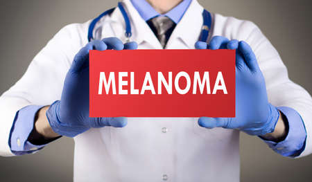 lesions: Doctors hands in blue gloves shows the word melanoma. Medical concept.