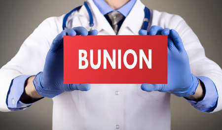 Doctors hands in blue gloves shows the word bunion. Medical concept.