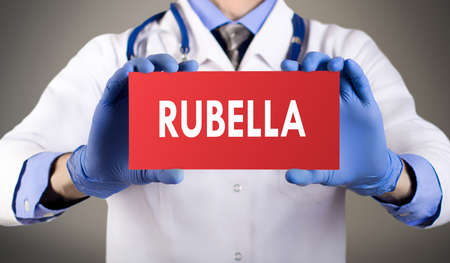 rubella: Doctors hands in blue gloves shows the word rubella. Medical concept. Stock Photo