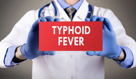 typhus: Doctors hands in blue gloves shows the word typhoid fever. Medical concept.