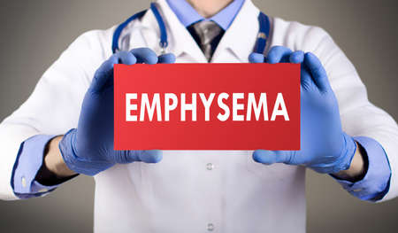 Doctors hands in blue gloves shows the word emphysema. Medical concept.