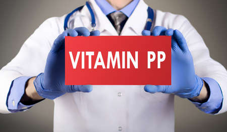 pp: Doctors hands in blue gloves shows the word vitamin pp. Medical concept. Stock Photo