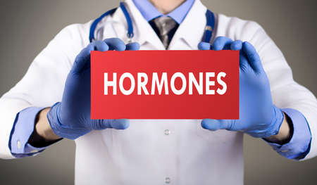 Doctors hands in blue gloves shows the word hormones. Medical concept.