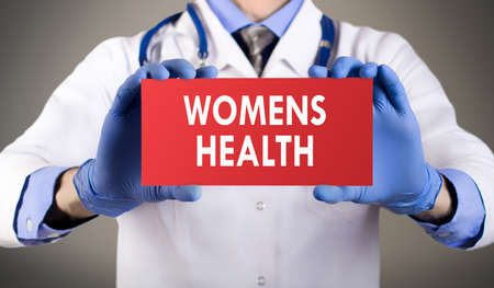 Women's health: Doctors hands in blue gloves shows the word womens health. Medical concept. Stock Photo