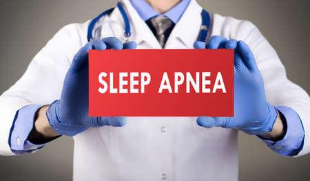 apnea: Doctors hands in blue gloves shows the word sleep apnea. Medical concept. Stock Photo