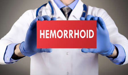 hemorrhoid: Doctors hands in blue gloves shows the word hemorrhoid. Medical concept.