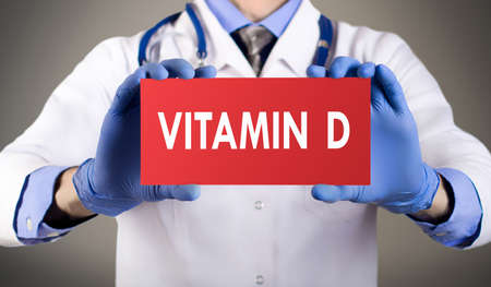 vitamin d: Doctors hands in blue gloves shows the word vitamin d. Medical concept.