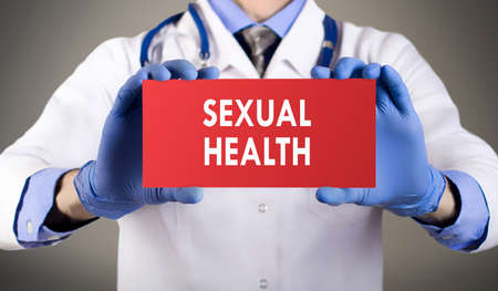 sexual health: Doctors hands in blue gloves shows the word sexual health. Medical concept.