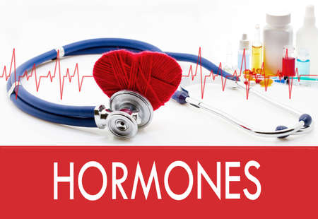 hormonas: Medical concept, hormones. Stethoscope and red heart on a white background Foto de archivo