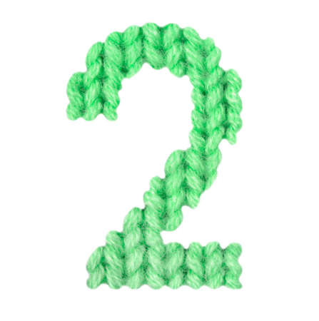Number 2 (two) alphabet on a blurry texture knitted pattern of woolen thread closeup. One figure of the alphabet. Education and holidays. Typography design. Color green