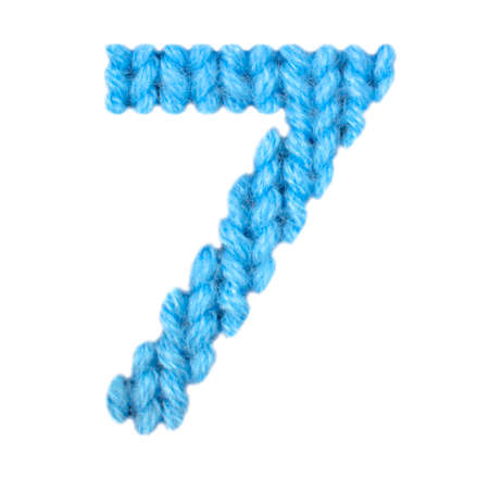 Number 7 (seven) alphabet on a blurry texture knitted pattern of woolen thread closeup. One figure of the alphabet. Education and holidays. Typography design. Color blue