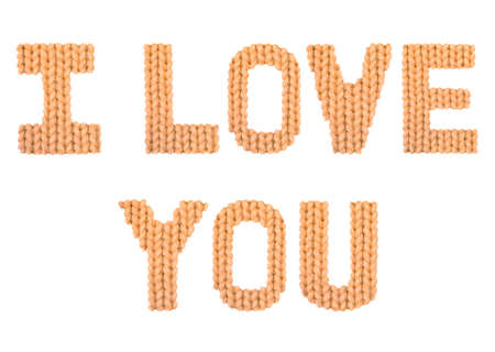 I love you word on a blurry texture knitted pattern of woolen thread closeup. English alphabet. Typography design. Color orange