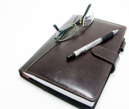 booked: day planner with eyeglass and pen for business