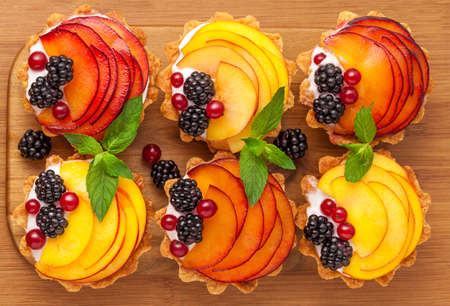 Tarts with froots on the wooden desk photo