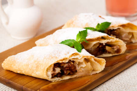 Strudel on the wooden board with mint photo