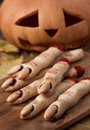 finger food: Halloween finger cookies and pumpkin Stock Photo