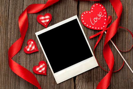 Empty polaroid photo frame with red hearts and ribbons for valentines day on wooden background photo