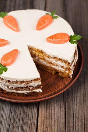 Sliced gourmet carrot sponge cake with icing cream and little orange carrots on vintage plate on wooden background photo