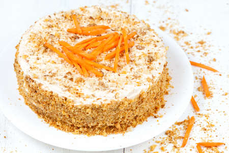 Fresh backed carrot sponge cake with walnut crumbs and carrots slices on white background photo
