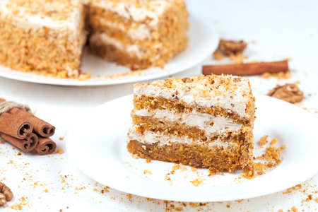 carrot cake: Slice of baked easter carrot cake with raisins and walnut on white background Stock Photo