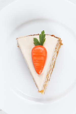 Piece of tasty carrot sponge cake with pastry cream and little orange carrots on top on white background photo