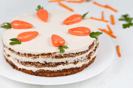 Delicious cheese cake with little carrots and cream op top on white background photo