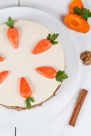 Delicious restaraunt carrot cake with cream and little carrots on white background photo