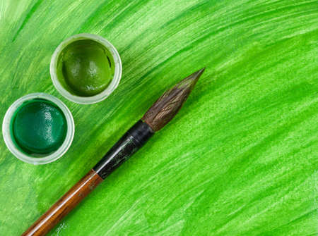 artist's canvas: Vintage artists paintbrush tool with two cups of gouache paint on green painted canvas background Stock Photo