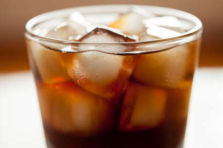 Cola sweet refreshment drink with ice cubes and bubbles in glass. Close up shot. Stock Photo