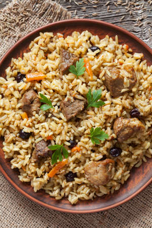 rise to the top: Pilaf is traditional delicious dish cooked from fried meat, lot of rise, carrot, onion, garlic and raisins. Top view closeup.