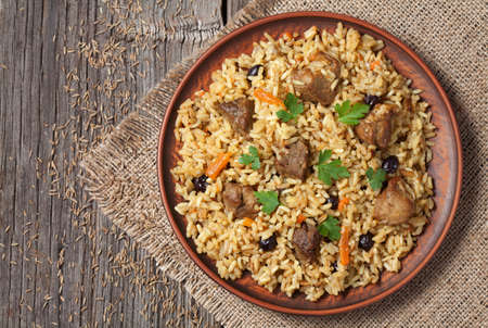 middle eastern food: Arabic national rice food called pilaf. Served in clay bowl on wooden table background.  Cooked with fried meat, onion, carrot and garlic