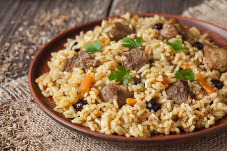 carrot: Cuenco de arcilla de la vendimia con la comida tradicional picante llamado pilaf, en el fondo de madera. Cocinado con frito de cordero, arroz, ajo, zanahoria y pasas.