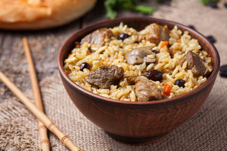 Traditional asian gourmet meal called pilaf cooked with rice, fried meat, carrot, onion and garlic. Served in clay bowl with food sticks