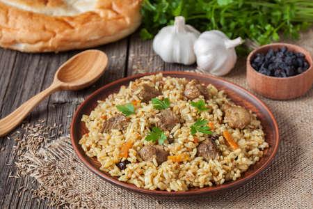 arroces: Comida tradicional uzbek llama pilaf. Arroz con carne, la zanahoria y la cebolla en la placa de la vendimia en el fondo de madera