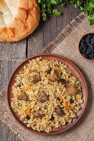 Plate of pilaf, traditional turkish spicy food with rice, fried meat, carrot onion and parsley. Served with fresh backed bread, raisins and vegetables. Archivio Fotografico