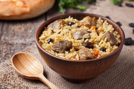 Traditional uzbek food called pilaf cooked with fried lamb meat, rice, carrot, onion and garlic. Served in clay plate with vegetables and wooden spoon
