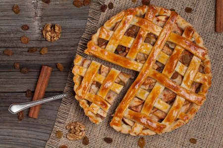 A piece of sliced apple pie with a metal spatula on vintage wooden background texture. Top view