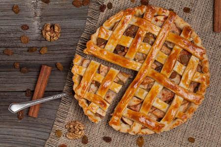 porcion de torta: Un pedazo de pastel de manzana en rodajas con una espátula de metal en la textura de fondo de madera de la vendimia. Vista superior Foto de archivo