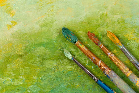 artist: Artists vintage tools brushes on green artistic background Stock Photo