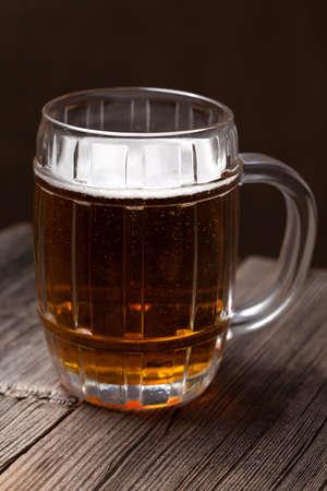 unbottled: Beer in glass on dark vintage wooden background for patricks day