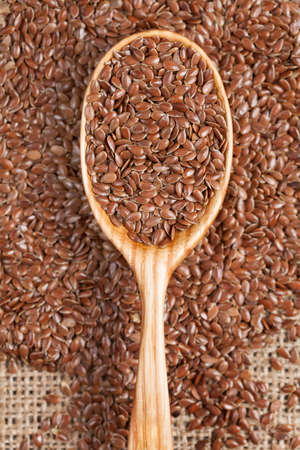 brown flax: Healthy little brown flax seeds super foods. Flax grain scattered on vintage textiles. Stock Photo