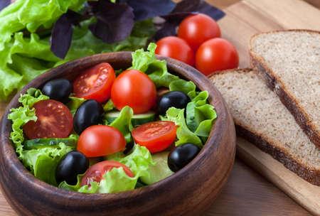 ensalada verde: Ensalada vegetariana saludable con tomate y aceitunas en el fondo r�stico